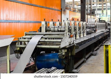 Modern machine for the manufacture of metal profiles. The main working bodies of the machine, metal rolls. Roller mill with many round steel rollers.