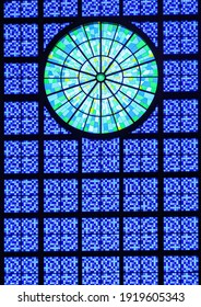 Modern main stained glass window of the National Sanctuary Basilica of Our Lady of Aparecida, in Brazil. Made of square shaped glasses with different bluish tones, and having a rosette of green tones.