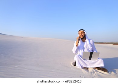 Modern male Arab and builder dials on cellular customer to clarify stages of construction and sits with computer on white clean sand outdoors on hot summer day. Smiling Muslim with short dark hair