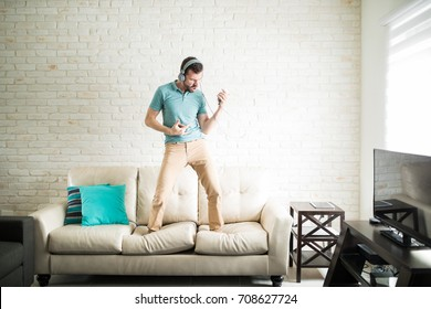 Modern man listening to music on his phone and standing on the couch playing an air guitar