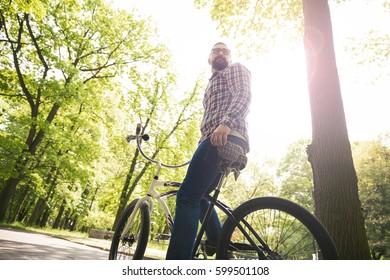 Modern man sitting on bike looking away at park