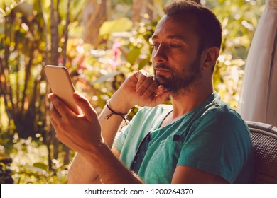 Modern man sitting in the tropical garden and using cellphone.
