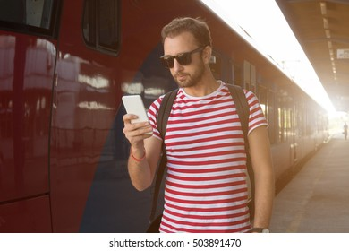 Modern man using cellphone on train station.
