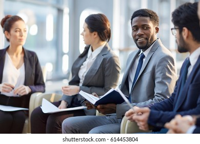 Modern manager looking at companion during business training or conference