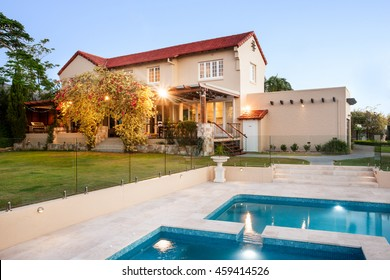 Modern mansion decorated with natural items like yellow trees and vines beside green grass lawn, garden and pool from the front