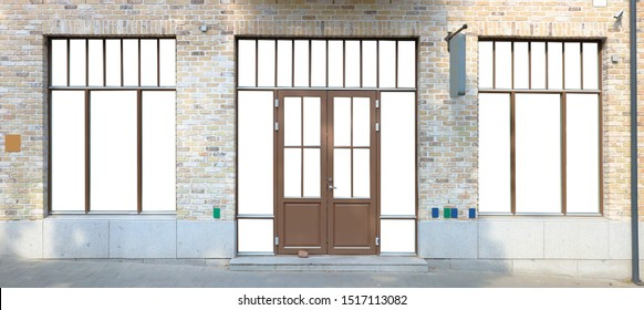 Modern mass production brown  plastic window frames and door is built in in a brick wall of the old but restored house. Glass isolated with white