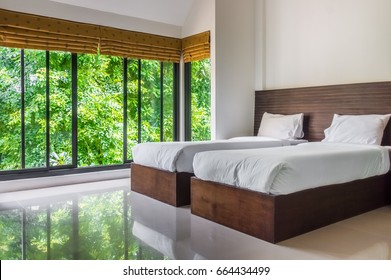 Modern master bedroom with twin beds and wide glass windows. The design to give scenic view of natural outdoor garden.
