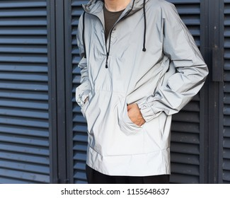 Modern materials in the fashion industry. Men's youth street fashion. Windbreaker from the rain. A man is posing in a fashionable silver jacket made of new technological materials. Part of the body.