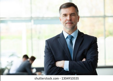 Modern mature businessman smiling and looking at camera with his colleagues in the background at office