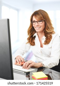 Modern Mature Businesswoman Sitting In The Office And Working On Her Computer
