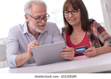 Modern mature couple shopping online with tablet and credit card