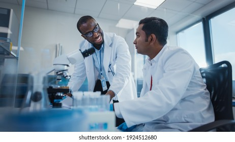 Modern Medical Research Laboratory: Two Smiling Male Scientists Working Together Using Microscope, Analysing Samples, Talking. Advanced Scientific Lab for Medicine, Biotechnology.