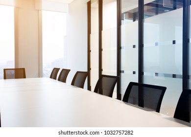 Modern meeting room with large windows, outside building, city, tower view, soft focus.