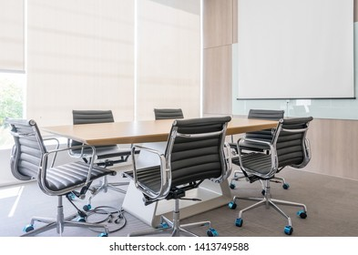 Modern meeting room with projection screen and conference table