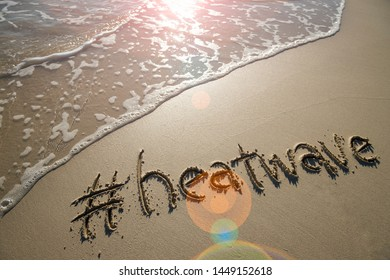 Modern message for the beach weather, heatwave, with a social media-friendly hashtag written in smooth sand with lens flare over an incoming wave