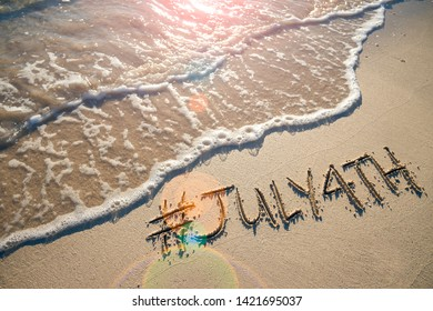 Modern message for the July 4th American holiday with a social media-friendly hashtag written in smooth sand with incoming wave on the beach