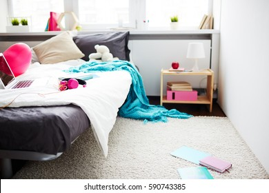 Modern messy bedroom of teenage girl: comfortable bed with laptop, headphones, blanket hanging down and school books lying on floor