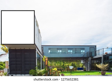 Modern metal building made from shipping house containers and blue sky background .empty white billboard .Blank space for text and images.