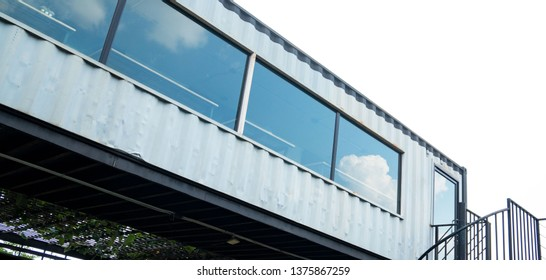 Modern metal building made from shipping house containers and blue sky background .
