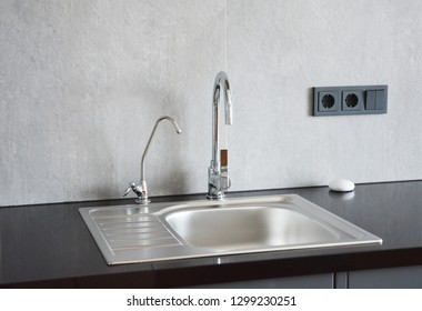 Modern metal kitchen sink. Modern kitchen chrome faucet and metal kitchen sink.