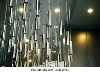 Modern metallic cylinder chandelier and black ceiling background