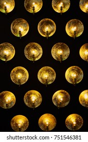 A modern metallic lamp with light bulbs on dark background. Shiny golden decorated inside lamp