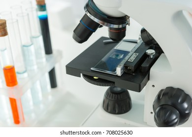 Modern microscope on the workplace near test tubes with liquid. Healthcare and biotechnology concept