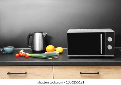 Modern microwave oven and ingredients on table in kitchen