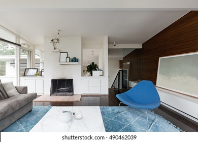 Modern mid century renovated living room with fireplace and blue rug