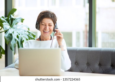 Modern middle-aged woman wearing, holding headset sitting at table in front of computer, looking at laptop smiling happily, laughing. Positive freelancer, customer service representative working happy