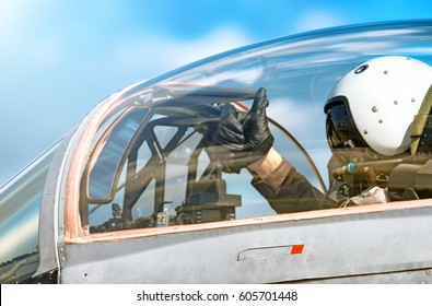 Modern military fighter jet aircraft canopy exterior close up silhouette view pilot waving OK gesture inside cockpit interior airplane parts sky glass reflection aviation aerial panoramic background