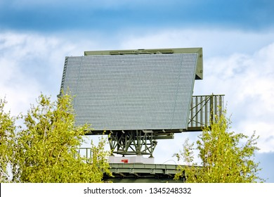 modern military radar antenna tower aerial close up view of satellite communication equipment radio station for air traffic control ATC technology against blue cloud sky landscape background