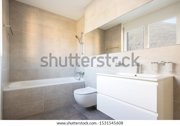 Modern minimal bathroom with large tile bathtub. Nobody inside