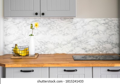 Modern minimal gray color kitchen with self adhesive fake marble imitation tape on wall, solid natural wood countertop with built in small stove.