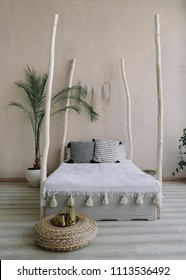 Modern minimal home interior design. Pillows, blanket, tropical palm tree, bed with wooden canopy. Exotic bedroom interior, scandinavian style