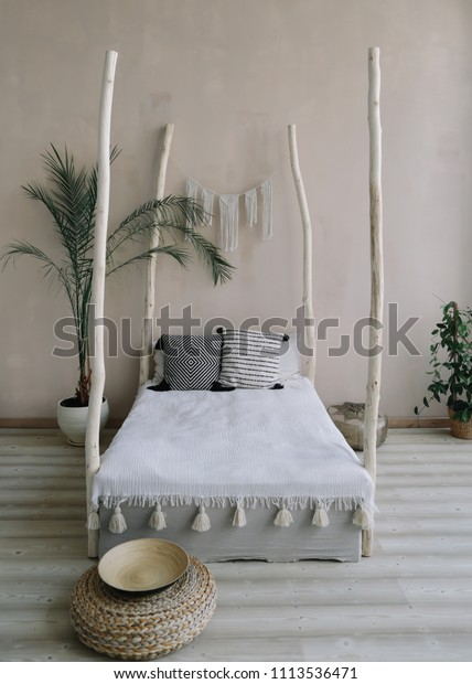 Modern minimal home interior design. Bed with wooden canopy and pillows, blanket, tropical palm tree. Exotic bedroom interior, scandinavian style