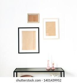 Modern minimal Scandinavian interior design concept decorated with mock up photo frames, bird figurine, rack on white background.