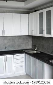 Modern minimalism style kitchen interior in monochrome tones. Custom kitchen with grey white facadesmdf and dark grey countertop with installed kitchen hood and sink. Modular kitchen from chipboard.