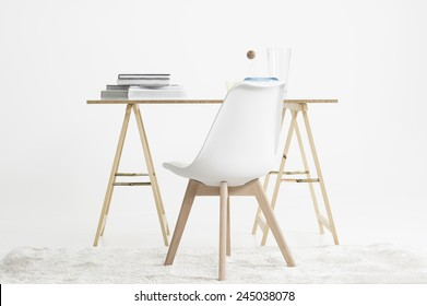 Modern minimalist desk or worktable on two trestles with a stack of magazines and books on top with a modular chair on a shaggy white carpet in a white room