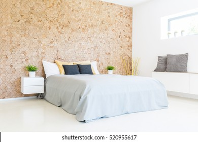 Modern minimalist eco-friendly bedroom with wooden wall and wide comfy bed