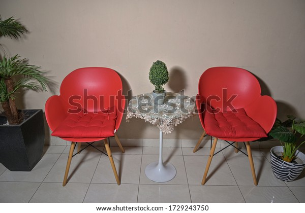 Modern minimalist red chair and round table with interior plant