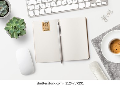 modern minimalist workspace / desktop with blank open notebook, coffee, office supplies and succulents on a white table -  top view