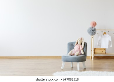 Modern minimalistic, kid's room with a grey, comfortable, chic chair and a stuffed animal sitting on it next to a wooden stand with a white t-shirt