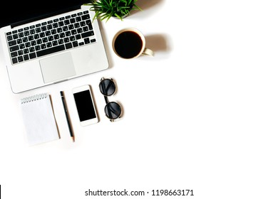 Modern minimalistic work place. White office desk table with laptop, smart phone, notebook, pen and pencil. Top view with copy space, flat lay