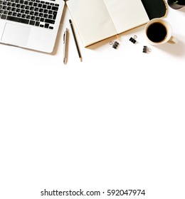 Modern minimalistic work place. White office desk table with laptop, coffee cup, clips, notebook, pen and pencil. Top view with copy space, flat lay