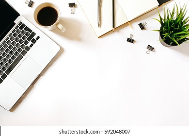 Modern minimalistic work place. White office desk table with laptop, coffee cup, clips, notebook, pen and penclil. Top view with copy space, flat lay