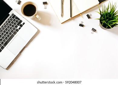 Moderner minimalistischer Arbeitsplatz. Weißer Schreibtisch mit Laptop, Kaffeetasse, Clips, Notebook, Stift und Stift. Draufsicht mit Kopienraum, flacher Hintergrund