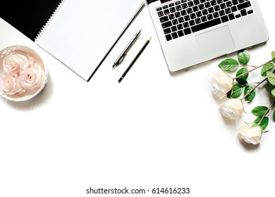 Modern minimalistic work place. White office desk table with laptop keyboard, pen, office plant, white roses, vintage tray. Top view with copy space, flat lay