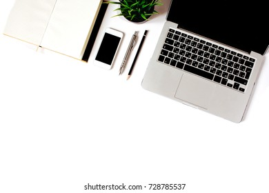 Modern minimalistic work place. White office desk table with laptop, smart phone, office plant, notebook, pen and pencil. Top view with copy space, flat lay, diagonal order