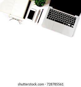 Modern minimalistic work place. White office desk table with laptop, smart phone, office plant, glasses, notebook, pen and pencil. Top view with copy space, flat lay, diagonal order